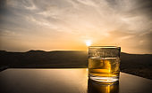 A glass of whiskey with ice on a sunset background or shot of whiskey at sunset dramatic sky on mountain landscape background