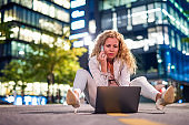 Woman sitting on the street using laptop and talking on mobile phone.