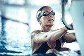 Female swimmer on starting block ready for backstroke swimming race