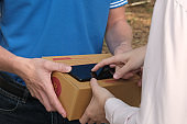 woman signing signature on smart phone to receive package from delivery man. male postal courier person deliver box