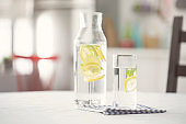 Water bottle and glass of water with lemon in kitchen