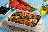 Eggplant casserole with mozzarella , tomatoes and olives.