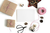 Christmas greeting card composition. Empty paper mock up, gift boxes, scissors, pine cones, isolated on white background.