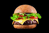 Big tasty hamburger or cheeseburger isolated on black background with grilled meat, cheese, tomato, bacon, onion. Burger closeup
