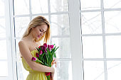 Young beautiful woman with tulip bunch in yellow dress. 8 march international womens day.