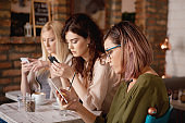Women using smart phones and drinking coffee in cafe.