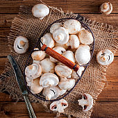 Raw fresh mushrooms in a metal basket on a wooden table, top view