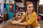 Calm woman sitting at the bar counter and turning her head