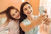Pretty teenage girls having fun while taking selfies