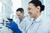 Positive asian woman studying dna model in a lab