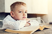 Sad little kid sitting with a book