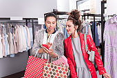 Attentive two friends overspending money on shopping