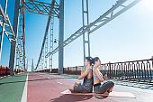 Beautiful serious woman and man meditating on bridge
