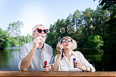 Funny elderly man wearing red heart shape sunglasses using soap bubbles