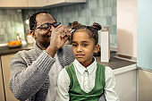 Caring cheerful father fixing hair slide on hair of his daughter