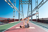 Concentrated man and woman trying couple yoga