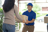 Woman receiving parcel from delivery man, delivery man brings delivering parcel box. Fast and reliable service.