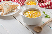 Corn soup in white bowl and toast with corn on white table.