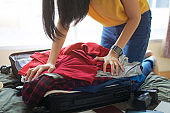 Woman pack clothes in suitcase bag on bed, prepare for new journey and travel to long weekend.