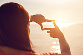 Woman hands making frame gesture with sunrise, Imagine Future
