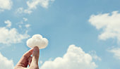 Woman hand holding cotton wool on cloud sky background. The development of the imagination.