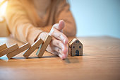 Woman hand stopping risk the wooden blocks from falling on house.