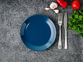 clean empty blue dark plate, fork and knife on gray concrete background, top view.