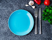 clean empty blue bright plate, fork and knife on gray concrete background, top view.