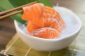 Chopsticks with Salmon sashimi with Salmon sashimi on ice in with bowl. japanese food in Asian restuarant.