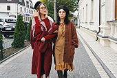 Women models in elegant autumn clothes and glasses over urban ci