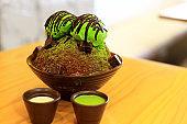 Closeup Matcha Green Tea Bingsu with green tea ice cream and chocolate and sweetened condensed milk remixes. Bingsu or Bingsoo is a Korean shaved ice dessert with sweet toppings.