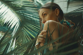 Portrait exotic woman among tropical plants, fashion, beauty, cosmetics, make-up.