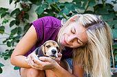 Woman cuddling with beagle puppy