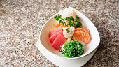 Japanese rice with mix sashimi don in a white bowl.