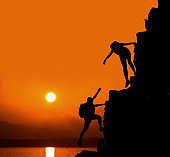 Silhouette sporty woman on the cliff. Sunset and high mountain. Business Success and teamwork