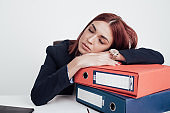 Tired businesswoman taking a nap on a pile of paperwork