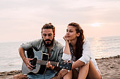 Couple with guitar at the beach