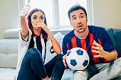 Surprised couple watching soccer game on TV