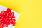 White gift box with red bow on yellow background with copy space