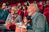 Couple at cinema with granddaughter