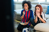 Female football fans with soccer uniforms making worried face expressions while watching a game