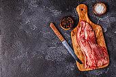 Portion of raw Bacon stripes on dark background