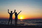 Silhouette picture of a loving couple holding hands at sunset on the sea