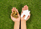 Conceptual picture hands holding white house and money over green grass field top view and copy space in Property investment Real estate Saving and buying home mortgage and loan banking concept.