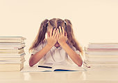 Frustrated little schoolgirl feeling a failure unable to concentrate in reading and writing difficulties learning problem attentional disorders special needs and low academic performance concept.