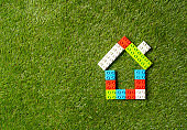 Conceptual picture of children toy blocks house on green grass field top view and copy space in Property investment Real estate Saving and buying home mortgage and loan Insurance and Banking concept.