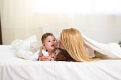 Portrait of young happy smiling mother with infant baby girl liying on the bed covered with a white blanket. Happy family concept