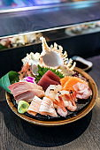 Selective focus decorated sashimi set in a bowl with ice and conch shell near the chef bar.