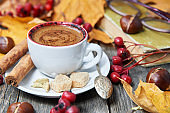 Hot steaming cup with coffee. Autumn fall leaves.