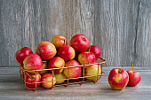 Red apples in basket on wooden background. Copy space